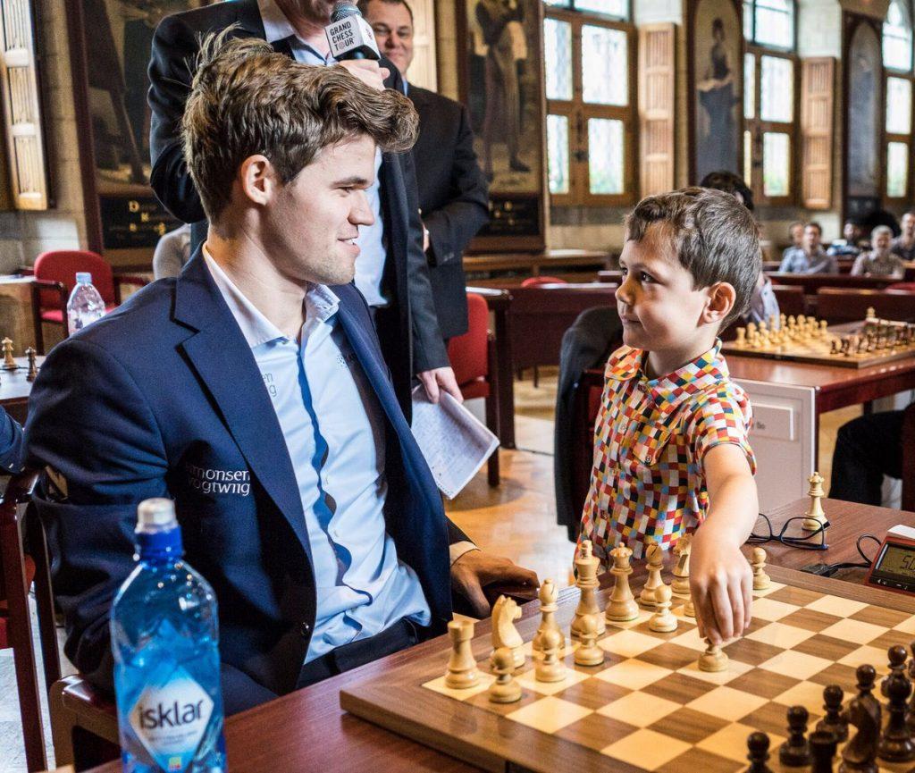 FAN: Magnus Carlsen fikk hjelp av fem år gamle Oliver til å utføre det første trekket i lynsjakken. Foto: Lennart Ootes