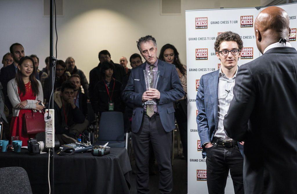 SEIERSINTERVJU: Fabiano Caruana intervjues av Maurice Ashley. Til venstre i bildet, i rødt, er 25-åringens stolte kjæreste. Foto: Lennart Ootes/Grand Chess Tour