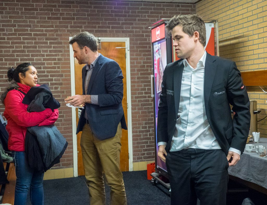 Magnus Carlsen leaving after his game, while Gawain Jones gets comfort from his wife Sue. Photo: Maria Emelianova