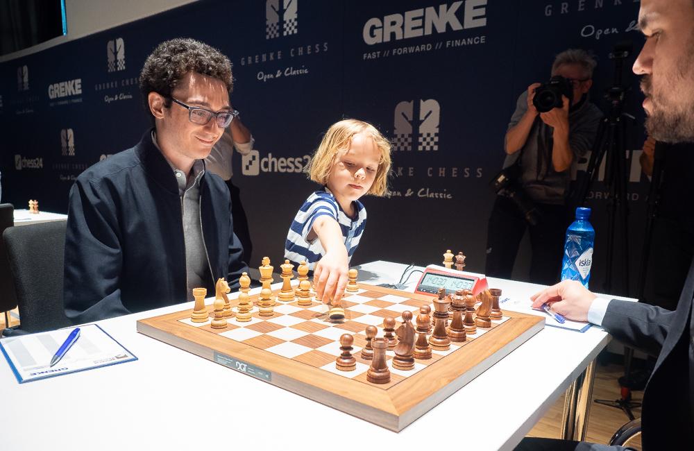 6 år gamle Alexander, turneringens yngste deltaker, utfører Fabiano Caruanas første trekk i møtet med Magnus Carlsen i Grenke Chess Classic 2019. Foto: Eric van Reem